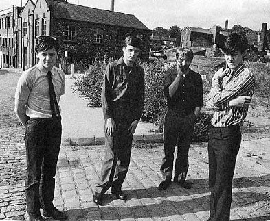 Joy Division promo photo; Curtis in striped shirt